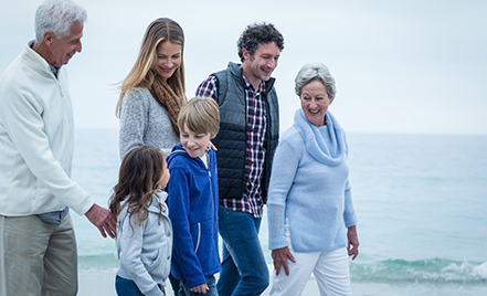 multi-generational family walking on beach